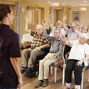Carer Leading Group Of Seniors In Adult Day Care program