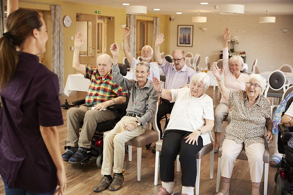 Carer Leading Group Of Seniors In Adult Day Care program